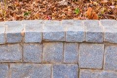 Le mur en pierre et sèchent des feuilles Photo stock