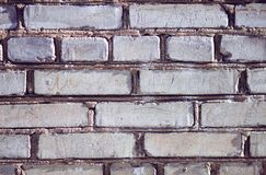 Le mur gris du bâtiment, construit des briques inégales rugueuses images stock