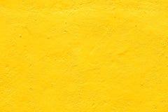 Le mur jaune de fond donne à rugueux une consistance rugueuse Photos libres de droits