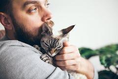 Le museau d'un chat et d'une barbe équipe le visage Plan rapproché de jeune homme beau et de chaton tigré photos libres de droits