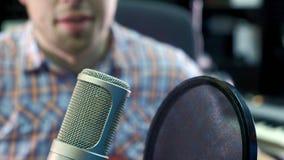 Le musicien créatif d'homme au studio travaille à côté de jouer, de chanter et d'enregistrer la guitare avec le carnet et le micr Image stock
