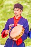 Le musicien de Kazak tient un tambour de basque dans des ses mains et le bat avec un batteur photos libres de droits