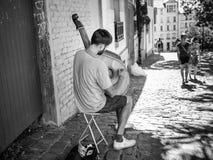 Le musicien de rue joue l'instrument ficelé sur le trottoir de Montmartre avec les couples de flânerie dans la distance moyenne,  Image stock