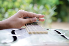 Le musicien expert joue une guitare de Dobro Photographie stock libre de droits