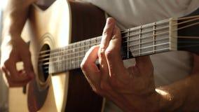 Le musicien joue le rythme sur une guitare acoustique jaune, pressant les ficelles avec ses doigts au barre banque de vidéos