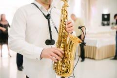 Le musicien joue le saxophone ? l'int?rieur en gros plan Le saxophoniste joue le saxophone au plan rapproch? d'?v?nement images libres de droits