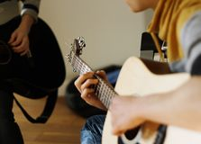 Le musicien joue un beige de guitare acoustique images stock