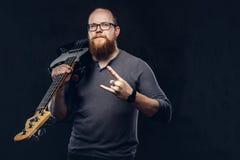 Le musicien masculin barbu roux portant des lunettes habillées dans un T-shirt gris tient la guitare électrique et le rock d'expo photos libres de droits