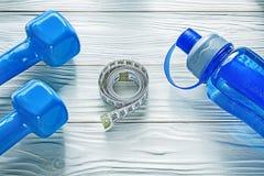 le Muto-campane hanno rotolato la bottiglia di acqua di misurazione del nastro sul bordo di legno fi Fotografia Stock Libera da Diritti