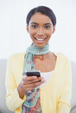 Le nätt kvinnasammanträde på soffatextmessaging Royaltyfri Bild