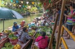 Le négociant et le client sur les bateaux en bois au Lat Mayom de Klong flottent le marché le 19 avril 2014 Photographie stock libre de droits