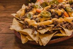 Le Nacho ébrèche le maïs garni avec le boeuf haché, fromage fondu, les poivrons de jalapeño, nourriture épicée mexicaine au Mexi images stock