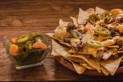 Le Nacho ébrèche le maïs garni avec le boeuf haché, fromage fondu, les poivrons de jalapeños, nourriture épicée mexicaine au Mex image stock