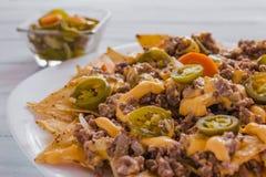 Le Nacho ébrèche le maïs garni avec le boeuf haché, fromage fondu, les poivrons de jalapeños, nourriture épicée mexicaine au Mex photos libres de droits