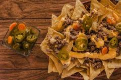 Le Nacho ébrèche le maïs garni avec le boeuf haché, le fromage fondu, nourriture épicée mexicaine de poivrons de jalapenos au Mex image stock