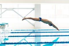 Le nageur sautant du bloc commençant i Image libre de droits