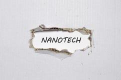 Le nanotech de mot apparaissant derrière le papier déchiré Images stock