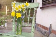 Le narcisse fleurit dans un vase sur une chaise verte images libres de droits