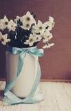 Le narcisse fleurit le bouquet dans la cruche décorée d'un arc bleu dans le style de vintage Photos stock