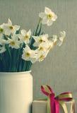 Le narcisse fleurit le bouquet dans le vase blanc et un boîte-cadeau dans le style de vintage Image libre de droits