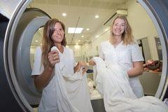 Le nettoyage à sec des employés charge la machine à laver professionnelle Photos stock