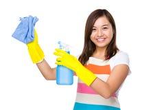 Le nettoyage de femme au foyer utilisant le chiffon et la bouteille pulvérisent Photographie stock