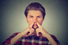 Le nez dégoûté de pincements d'homme avec des doigts quelque chose empeste la mauvaise odeur Image stock