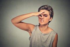 Le nez de pincements de femme avec des regards de doigts avec dégoût loin quelque chose empeste la mauvaise odeur image stock