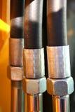 Le noci chromeplated ed i tubi flessibili di rinforzo di idraulico Fotografia Stock Libera da Diritti