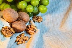 le noci e l'uva verde si trovano sul panno di tela immagini stock libere da diritti