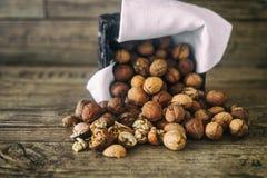 Le noci fresche si rovesciano da un canestro di vimini sul fondo sulla vecchia tavola di legno, cocept sano di autunno del cibo Fotografie Stock
