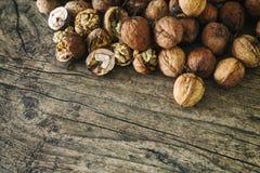 Le noci fresche si rovesciano da un canestro di vimini sul fondo sulla vecchia tavola di legno, cocept sano di autunno del cibo Fotografia Stock