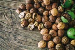 Le noci fresche si rovesciano da un canestro di vimini sul fondo sulla vecchia tavola di legno, cocept sano di autunno del cibo Immagine Stock Libera da Diritti