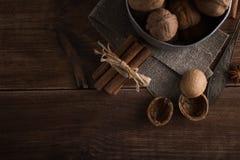 Le noci in un metallo lanciano, fondo scuro Coperture e cannella della noce sulla tavola di legno Immagine Stock