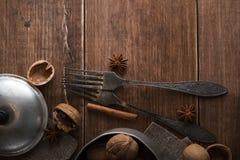 Le noci in un metallo lanciano, fondo scuro Coperture e cannella della noce sulla tavola di legno Immagine Stock Libera da Diritti