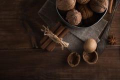 Le noci in un metallo lanciano, fondo scuro Coperture e cannella della noce sulla tavola di legno Immagini Stock