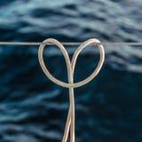 Le noeud d'accroc de noeud de corde sur un câble en acier, en forme de coeur sur le fond de l'océan Photos stock