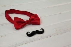 Le noeud papillon et la moustache de faux ont arrangé sur la planche en bois Photographie stock