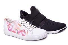 Le noir des hommes et les chaussures blanches du sport des femmes Images stock