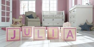 Le nom Julia écrite avec les cubes en bois en jouet chez la pièce du ` s des enfants Photo stock