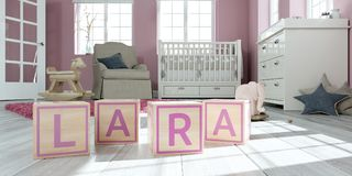 Le nom Lara écrite avec les cubes en bois en jouet chez la pièce du ` s des enfants Photographie stock