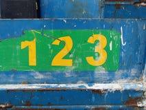 Le nombre grunge se connecte le fond métallique bleu Photographie stock libre de droits