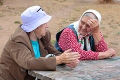 Le nonne del pensionato stanno sedendo alla tavola Fotografia Stock