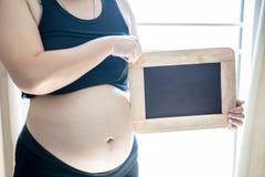 Le note gialle in bianco dell'autoadesivo sul ` s della donna incinta si gonfiano Concetto del FAQ Immagini Stock