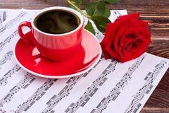 Le note musicali con la tazza rossa e sono aumentato Immagini Stock