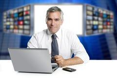 Le notizie grige dei capelli TV selezionano sorridere del computer portatile del presentatore fotografia stock libera da diritti