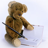 Le nounours antique écrit avec un stylo-plume dans un livre Photographie stock