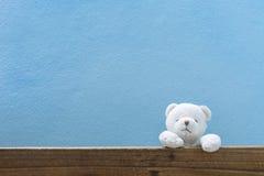 Le nounours concernent le vieux bois et le fond bleu de mur Photos libres de droits