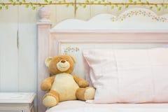 Le nounours concernent un lit rose photo stock