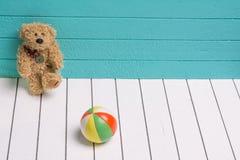 Le nounours concernent un plancher en bois blanc à l'arrière-plan bleu-vert jouant avec la boule Photos stock